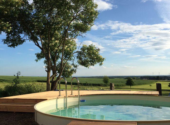 pool-im-garten-holzterasse-la%cc%88rche-rund-sandfarben